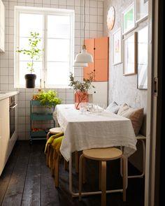 Det samme lille køkken er nu indrettet til gæster med et dækket bord, en bænk og stabelbare taburetter.