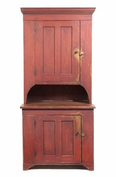 An American Painted Pine Step Back Cupboard, the superstructure having a molded cornice above a single coffered door, the base with a coffered door, raised on bracket feet. Height 81 x width 37 x depth 21 inches.  Property from the Estate of Bettie Blunt, Oak Creek, Wisconsin