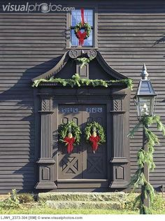 A Colonial Clapboard with Double Doors Decorated with Wreaths and Garlands of Pine.