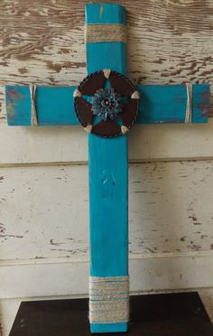 A hand-painted cross crafted from scrap wood. This piece is rustic with a touch…