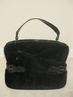 VINTAGE 1950's KORET GENUINE CALFSKIN LEATHER HANDBAG WITH ATTACHED COIN PURSE. It is made of genuine black calfskin leather, the exterior is covered in black calf fur, and has a gold clasp at the top to close. The bag measures approximately 13 inches wide and 11 inches tall the Koret name is featured inside the bag. It is a 50's style with a gold snap closure at the top.