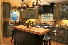 "This kitchen features a 3"" butcher block for a raised working height. Antique chandeliers were converted into down lights over the island. Dan Davis Design, LLC"