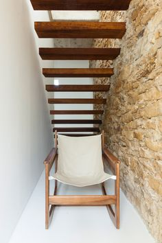 A staircase with cantilevered treads is supported by the stone wall, which contrasts with the white surface opposite it.
