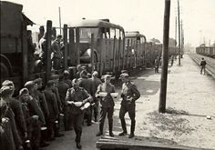 German troops lining up to fill their mess tins at a field kitchen mounted on a train - World War II