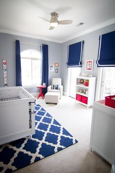 Boxy, contemporary furniture mixed with classic window treatments create a stylish, kid-friendly space for a modern family. Gray walls are a chic, neutral backdrop for red accents, and a graphic rug pulls the space together. The classic style of the space is designed to age well with the room's occupant.