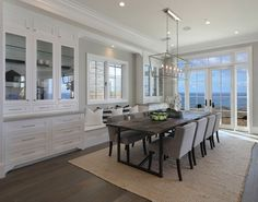Dining room with builtin hutch cabinet, built in window seat and French doors to a backyard with ocean view #diningroom #builtinhutch #hutch #windowseat Brandon Architects, Inc