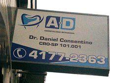 Placa para fachada de dentista feita em caixa de alumínio e lona impressa em alta resolução por Foco Design & Gráfica.