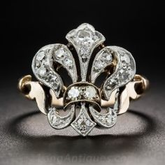 Hand-fabricated in platinum over 9K gold (hence of British origin), around the turn-of-the-last-century, this charming Edwardian jewel, artfully fashioned as a French fluer-de-lis, glitters with small single-cut diamonds. Unknown maker but numbered (01187) inside the currently size 5+ ring shank. 5/8 inch.