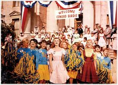 Altho filmed/released in 1963, Bye-Bye-Birdie was based on the 1956 events in Jacksonville Florida when Elvis came to town to plant a kiss on a prize-winning teen. With a little theatrical license, the movie also included Elvis' induction into the Army. The costumes in this movie are spot on. I made a Tyrolean jumper just like that one, worn teen on right, in 1956 - and even paired it with a yellow blouse. One of the best movies to re-visit the 50's!