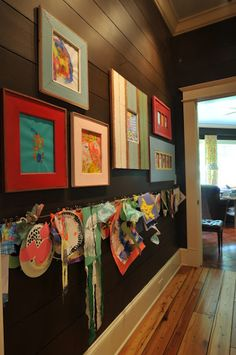 kids art on display.  I love the dark walls with the colorful frames!