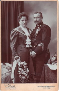 A soldier and his bride pose for their wedding portrait at the studio of Balde, located in either Salzburg, Wildbad, Gastein, Znaim or Retz. These cities are located in different countries; Austria, Germany and Czech Republic. The studio was formerly known as Wagner & Leeb. The soldier in this photograph has been identified as German by the former owner of the image, but the accuracy of this identification is uncertain.