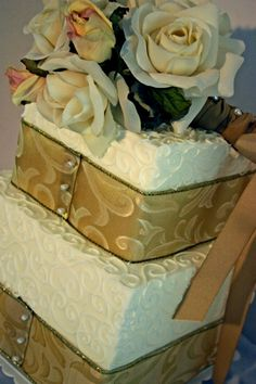 Two-tier square cake with ribbon and curlicue piped detailing