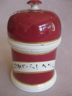 """A cherry red  ceramic Pharmacy  domed lidded pot with a liner.A crescent shaped gilt lined cartouche with the ingredient label worn.  English  Circa  1880 Height 6"""""""