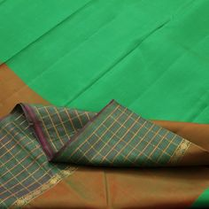 The refreshing plain aquamarine #silk body comes with an unusual dual border: a thick slice of burnished copper-green flows like a rivulet of murky waters atop the moss green embankment with precise gold checks and pebble-sized rudraksh motifs. The pallu is a riot of colours with moss green checks framing burnished copper stripes and azure blue. For #Kanjivarams in this alluring green, visit Sarangi. Code 180124560.