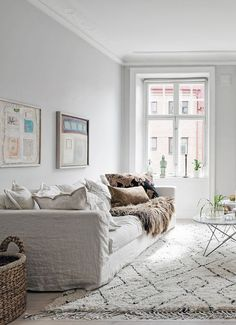 white scandinavian style living room | grey walls and white floors | white linen sofa with loads of cushions | Copy the look with an IKEA Karlstad sofa with a Bemz Loose Fit Urban cover in Absolute White Rosendal Linen