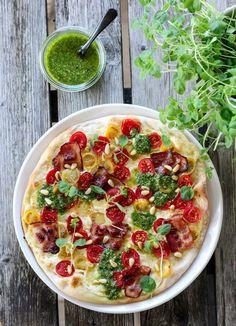 Idag kan jeg friste med en fargerik og smakfull hvit pizza, som er toppet med cherrytomater i ulike farger, bacon, pinjekjerner og en deilig basilikumpesto. Prøv den du også!