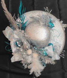 Straw hat spray painted silver inside and out.  Add feathers, wired ornaments, ribbon and other delights.  Perfect for the front door.