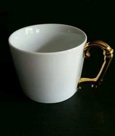 Perfect for coffee, tea, latte, cocoa or add to your collection for display. Cup has smooth plain white exterior and interior and a gold handle. Some wear on top of handle.
