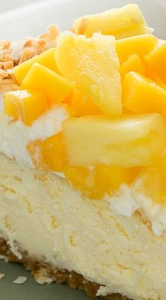 This light and fluffy Coconut Cheesecake is topped with fresh whipped cream and a pile of tropical mango and pineapple, which is sure to put a smile on anyone's face. Coconut Cheesecake, Cheesecake Recipes, Dessert Recipes, Pineapple Cheesecake, Cheesecake Bars, Cupcakes, Brownies, Toasted Coconut, Cheesecakes