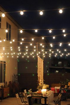 "Stringing lights over a table creates a ""ceiling"" and turns a fairly plain setup into an elegant outdoor dining area... outdoor lights strung over table area..remember. Still have lights leftover from party"