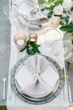 Chic outdoor wedding reception place setting, light blue plates, white fabric table runners, cream floral centerpieces, candles, light grey linens, silver flatware // Sera Petras Photography