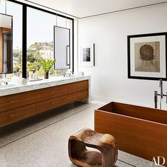 An Aero stool sits beside an Agape tub in the master bath, which features marble mosaic floor tile by Waterworks | archdigest.com