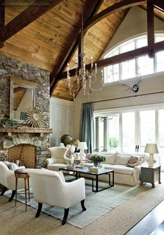 This is my dream living room....high ceilings, stone fireplace, wood panels on the ceiling, large windows, etc etc etc!