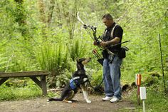 U.S. Army Spc. Mike Ballard stands with Apollo, his service dog, during an archery shooting session, on May 17, 2012, in Puyallup, Washington. Ballard says his dog helps him get through the worst symptoms of the post-traumatic stress disorder that are a remnant of an explosion in Afghanistan that ended his career as an Army medic. (AP Photo/Ted S. Warren)