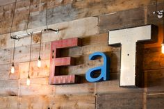 Reclaimed channel letter Eat signage mounted on interior wall to reclaimed barn wood with exposed filament bulb lighting.