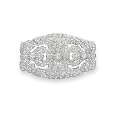 AN ART DECO DIAMOND BROOCH -  Designed as an openwork circular and baguette-cut diamond geometric plaque, bezel-set with three larger circular-cut diamonds, mounted in platinum, circa 1920.