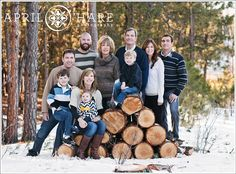 An extended family portrait taken with a stack of firewood in the grandparent's woodsy backyard at their family photo session in Monument Co...