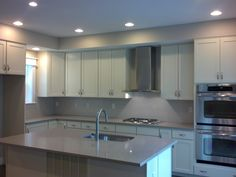 Finished kitchen.  GE Profile hood, GE appliances, Caesarstone counters, white cabinets