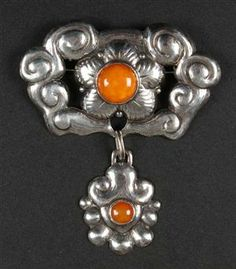 C. Mortensen. Skonvirke brooch of silver chased with flowers and ornaments and adorned with amber. 1920. H. 7.5 B. 6.5 cm. View 1.