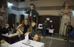"A child deposits her mother's ballot at a polling station in a school in front of Catalan ""Gegants"", or giant figures, while voting in a symbolic independence vote in Barcelona, November 9, 2014. REUTERS/Paul Hanna"