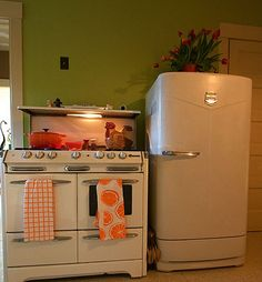 LOVE - this retro fridge and stove are perfect!  Love the green kitchen paint color on the wall and the pop of orange with dutch oven!