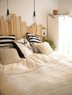 Wood plank head board, creams, striped and deer throw pillows.