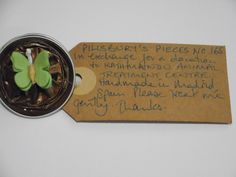 Pillsbury?s Pieces No, 165.  Pin - metallic milk chocolate brown capsule with pale khaski green paper butterfly.  In exchange for a donation to KATHMANDU ANIMAL TREATMENT CENTRE, Nepal.  Available at St. George's Church, Madrid on Saturday 13 June from 11.00 - 15.00.