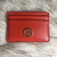 Tory Burch leather card case Gently loved and still in excellent condition. Some marks on the back from use and some wear to emblem (to be expected from going into a pocket or other bag). Orange saffiano leather. 4 card slots and big interior pocket for cash.❗️NO TRADES / LOWBALLING❗️ Tory Burch Accessories Key & Card Holders
