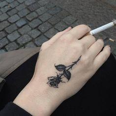 Tatuaje de una pequeña rosa en la mano. Artista tatuador: Kane...
