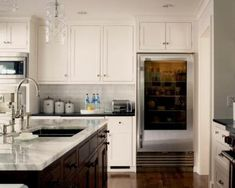 I think white cabinets would be good bc of the lack of sunlight and windows in the kitchen area. This would be the ideal combo of things!    Modern kitchen design with creamy white kitchen cabinets with espresso stained kitchen island, white carrara marble counter tops, white subway tiles backsplash, polished chrome fixtures