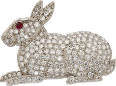 The brooch features full-cut diamonds weighing a total of approximately 6.00 carats, enhanced by a ruby cabochon weighing approximately 0.10 carat, set in platinum. Gross weight 29.80 grams. Dimensions: 1-15/16 inches x 1-7/16 inches Estimate: $3,000 - $4,000.