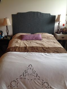 Create your own simple and inexpensive headboard. All you need is material or sheet to cover a large strong piece of cardboard. Cut out the design you like and cover. Use a regular stapler and tape to secure material to cardboard.