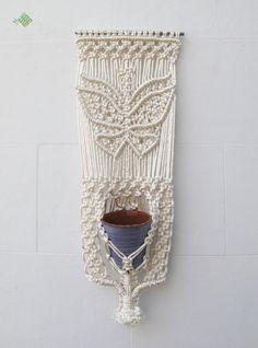 Un tapiz-macetero elaborado en cuerda de rayón, con un motivo de mariposa