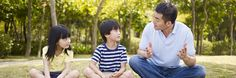 Father talks to daughter and son as tehy sit outside on grass