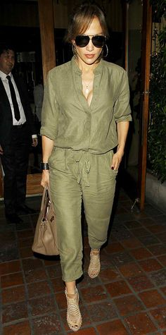 Jennifer Lopez stepped out in a chic military-inspired ensemble, courtesy of a utilitarian olive green jumpsuit that she styled with a delicate pendant, hoops, aviators, a strong cuff, and neutral accessories.