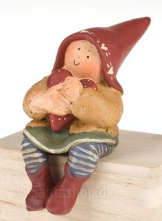 """I serien med de søde Fortune Fairies af Annakabouke finder du her """"Lykkefe for kærlighed"""". Feen sidder og krammer et hjerte og tænker på sin udkårne. Lykkefeen er 10 cm høj og leveres i en lille """"bog"""" med silkebånd. Ligger godt pakket ind i skumgummi, så den er let at sende. En sød lille kærestegave for at udtrykke sin kærlighed."""