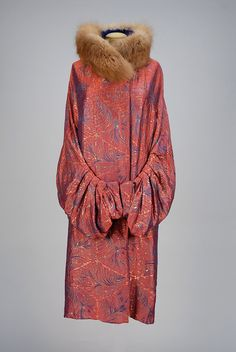 CHANGEABLE SILK and METALLIC BROCADE EVENING COAT, 1920s. Red and blue brocaded with blue and metallic gold stylized feathers, sleeve shaped with a series of box pleats, cobalt velvet lining. Label: Gunther Furs Paris New York.
