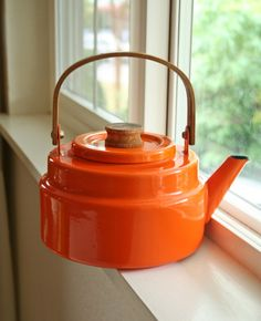 orange enamelware tea kettle with wooden handle
