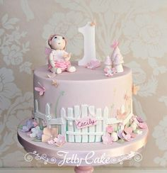 A pretty cake for my gorgeous Niece's 1st birthday. Painted grass around the sides of the cake with a white picket fence and gate. Lots of sugar flowers, butterflies and toadstools, topped with a sugar model of Cecily in her tutu and fairy wings!