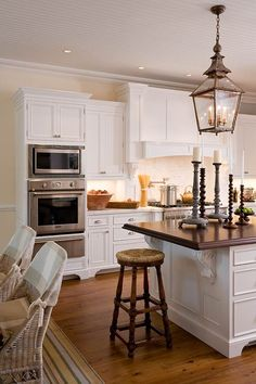 """Kitchen Cabinets with Furniture-Style Flair - Traditional Home®; not into the """"corbels"""" but like the simple crown molding at the top of these cabinets plus love the oven/ micro/warming drawer combo"""